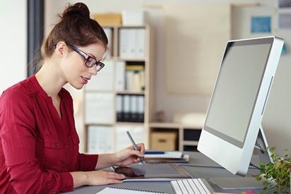 Frau mit Brille arbeitet vor PC