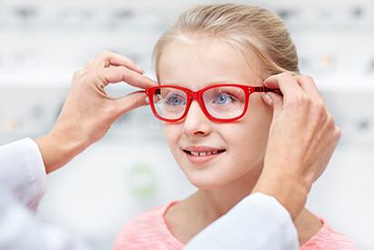 Mädchen mit roter Kinderbrille beim Augenarzt