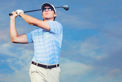 Golfspieler mit Golfbrille macht den Abschlag